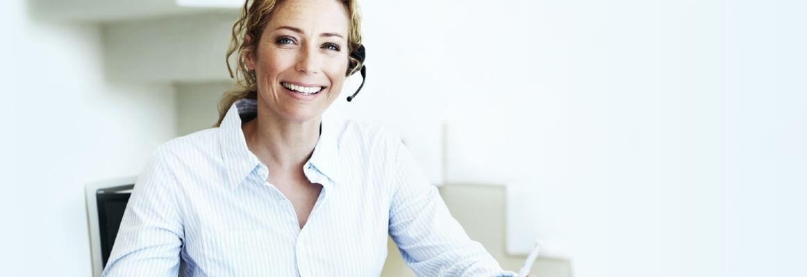 Frau mit Headset am PC