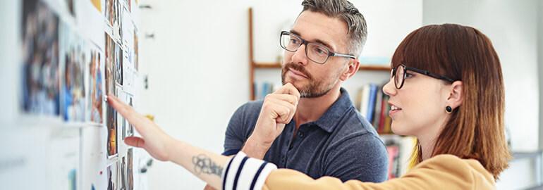 Zwei Personen lernen neue Marketing-Skills an einem Moodboard
