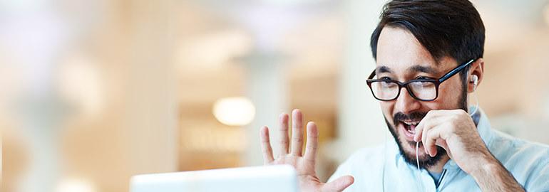 Ein selbstbewusster Mann spricht über Kopfhörer in einen Laptop